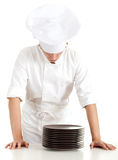 Male cook with stack of brown plates Royalty Free Stock Photos