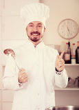 Male cook tasting food. Smiling man cook tasting delicious dishes in kitchen Royalty Free Stock Images