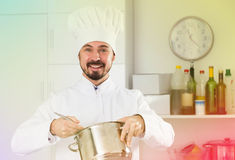 Male cook tasting food. Smiling man cook tasting delicious dishes in kitchen Royalty Free Stock Photo