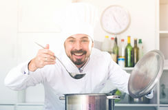 Male cook tasting food. Young male cook tasting food while preparing in kitchen Stock Photos