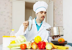 Male cook in uniform cooking with vegetables Royalty Free Stock Photography