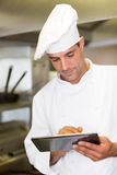 Male cook using digital tablet in kitchen Royalty Free Stock Images