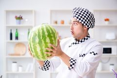 The male cook with watermelon in kitchen Royalty Free Stock Images