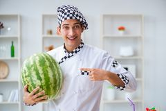 The male cook with watermelon in kitchen Royalty Free Stock Image
