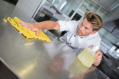 Male cook wiping counter top in kitchen. Male cook wiping the counter top in the kitchen Stock Photography