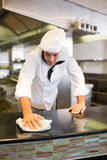 Male cook wiping kitchen counter Stock Image