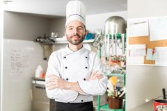 Male Cook Working In Restaurant. Portrait of Hispanic Latin chef in uniform standing in commercial kitchen stock image