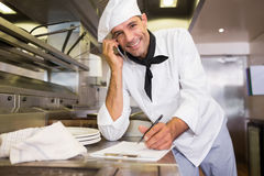 Male cook writing on clipboard while using cellphone in kitchen Royalty Free Stock Image