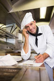 Male cook writing on clipboard while using cellphone in kitchen Royalty Free Stock Photos