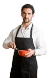 Male Cooker With Apron Smiling. Male cooker with a black apron, smiling and holding a egg-beater, isolated in white Stock Photography