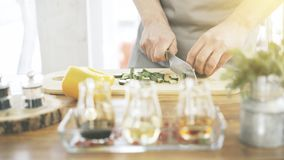 Male cooker`s hands slicing cucumbers on a wooden cooking board. Close up of male cookers hands cutting slicing cucumbers on a wooden kitchen board olive and Royalty Free Stock Photos