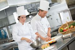 Male cooks preparing dishes in restaurant kitchen stock photo