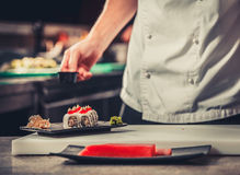 Male cooks preparing sushi Stock Photos