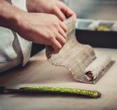 Male cooks preparing sushi Stock Image