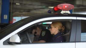 Male cop sitting into patrol car to his female partner and they driving to call stock video