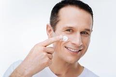 Positive nice man using facial cream Stock Photography