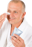 Male cosmetics - senior man apply facial cream Stock Images