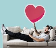 Male on a couch holding a heart emoticon stock photos