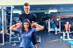 Male couch trains young woman in sportswear lifting some weights Stock Images
