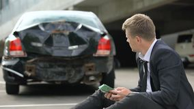 Male counting euros, looking at damage car after traffic accident, repairs cost. Stock footage stock footage