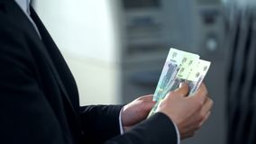 Male counting rubbles withdrawn from ATM, good service, business trip to Russia. Stock photo stock photography