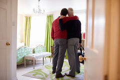 Male couple with arms around each other arrive in hotel room Royalty Free Stock Photography