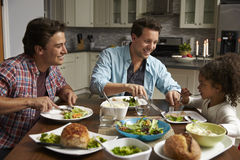 Male couple and black daughter dining in their kitchen stock photo