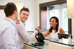 Male Couple Checking In At Hotel Reception Royalty Free Stock Photography
