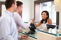 Male Couple Checking In At Hotel Reception Stock Photo