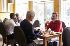 A male couple eating at a table in a busy restaurant Stock Photo