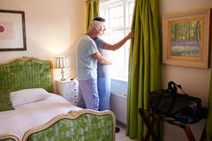 Male couple embrace looking out hotel room window, full length Royalty Free Stock Photography