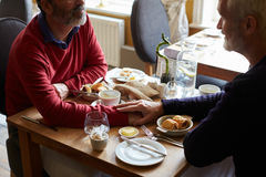 Male couple hold hands at a restaurant table, elevated view Royalty Free Stock Photos