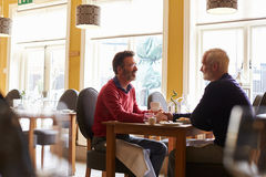 Male couple hold hands at a restaurant, three quarter length Royalty Free Stock Images