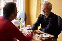 Male couple holding hands at restaurant, over shoulder view Royalty Free Stock Image