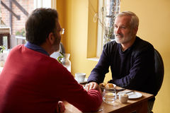 Male couple holding hands at restaurant, over shoulder view Stock Images