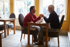 Male couple holding hands at a restaurant table, full length Stock Photography