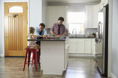 Male couple preparing a meal talk to their daughter in kitchen Stock Photo