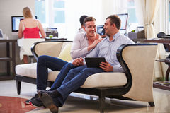 Male Couple Sitting In Hotel Lobby Looking At Digital Tablet Royalty Free Stock Images