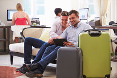 Male Couple Sitting In Hotel Lobby Looking At Digital Tablet Royalty Free Stock Photos