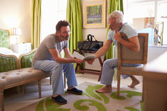 Male couple wearing pyjamas in a hotel room plan their day Royalty Free Stock Image