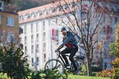 Male courier with electric bicycle delivering packages in city. Male hipster courier with electric bicycle delivering packages in city stock photography