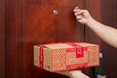 Male courier from JD.com delivering a parcel with Chinese New Year things and knocking the door. Zhongshan,China-January 25, 2017:male courier from JD.com Stock Photos
