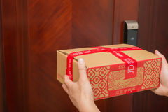 Male courier from JD.com delivering a parcel with Chinese New Year things. Zhongshan,China-January 25, 2017:male courier from JD.com delivering a parcel with Royalty Free Stock Images