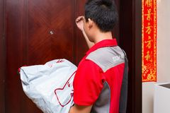 Male courier from JD.com delivering a parcel to the customers home. Zhongshan,China-April 20,2018:male courier from JD.com delivering a parcel to the customers stock image
