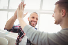 Male coworkers giving high-five Stock Photo
