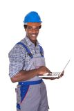 Male craftsman holding laptop Stock Images