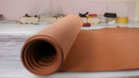 Male craftswoman rolling sheet of leather on table in workshop or private manufacture of clothing and accessories. 4 k