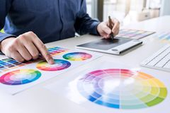 Male creative graphic designer working on color selection and color swatches, drawing on graphics tablet at workplace with work. Tools and accessories stock photos