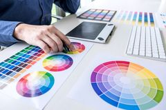 Male creative graphic designer working on color selection and color swatches, drawing on graphics tablet at workplace with work. Tools and accessories royalty free stock image