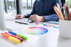 Male creative graphic designer working on color selection and color swatches, drawing on graphics tablet at workplace with work. Tools and accessories royalty free stock photography